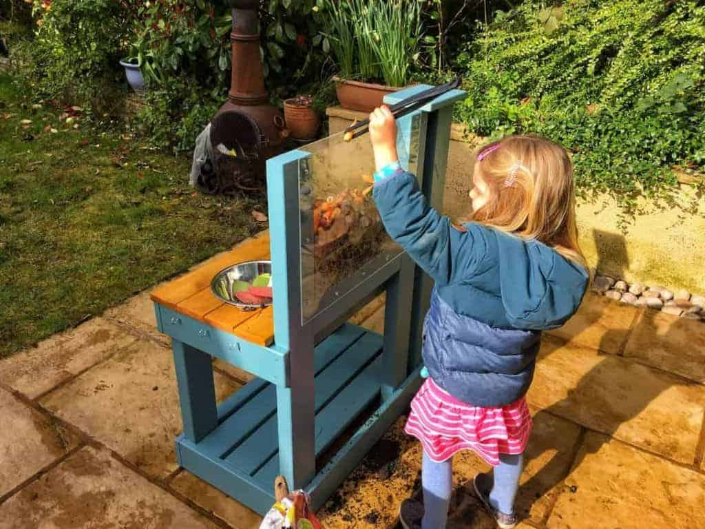 Girl playing outside with worm mud kitchen