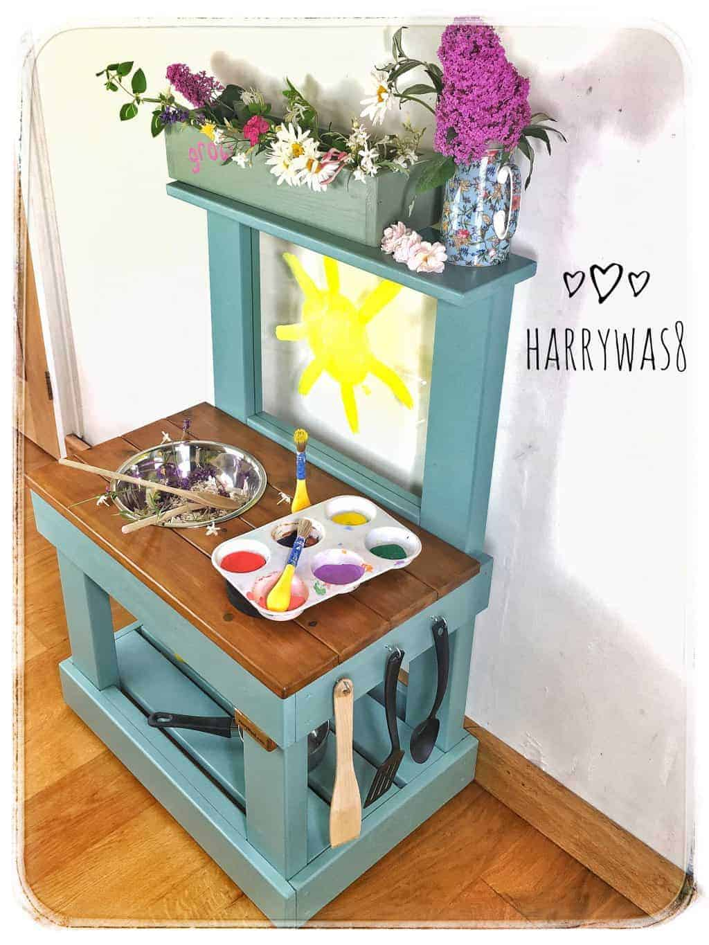 Side view mud kitchen with flowers and art easel
