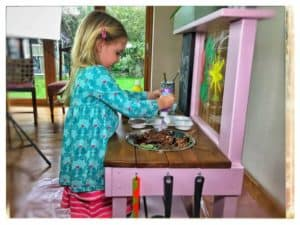 Mud Kitchens with art easel girl painting